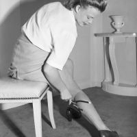 """Drawing in the seam-line on """"Makeup"""" stockings with a device made from a screw driver handle, bicycle leg clip, and an eyebrow pencil, 1942. Bettman/Corbis."""